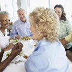 group of older people round table eating