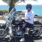 man on motorbike on seafront in front of palm tree