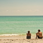 Couple sitting on the sand with the ocean in the background on a hot sunny day