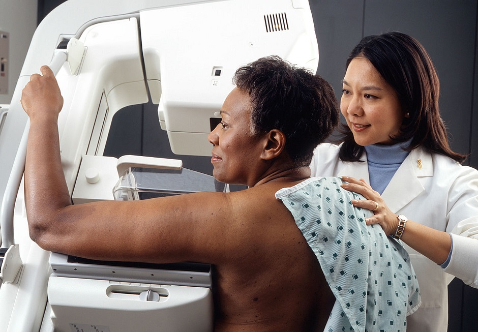 Lady being assisted in a Mammogram by female doctor testing cancer link