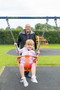 grandfather pushing grandchild on swing