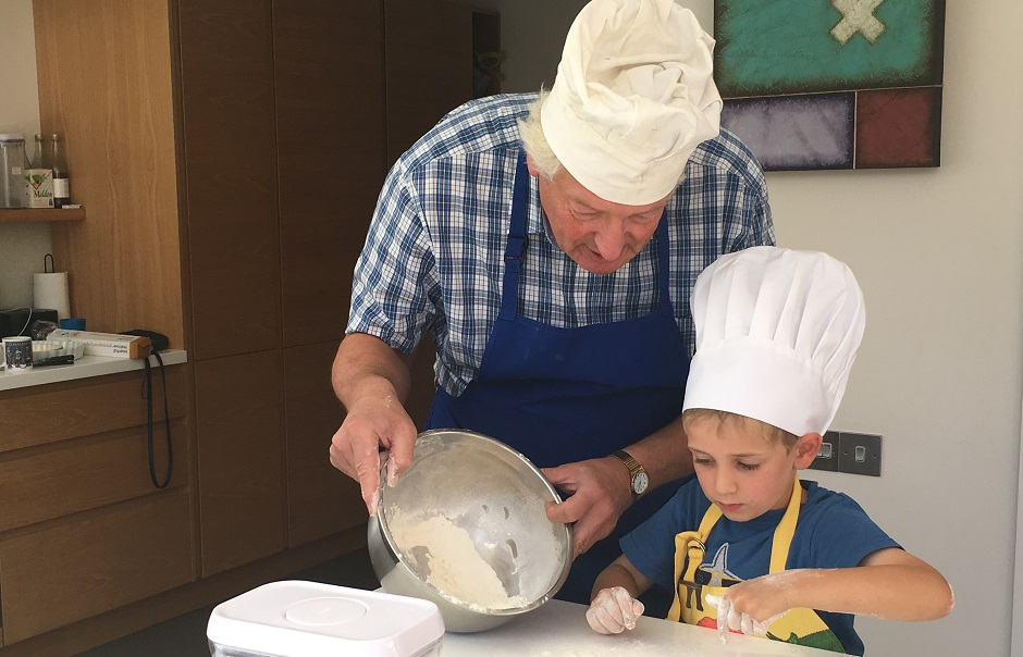 Grandfather cooking with grandchild