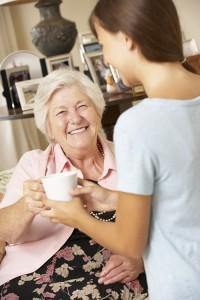 carer handing old lady mug of tea