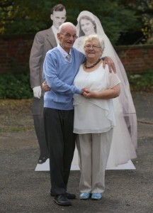 elderly couple next to cardboard cut out of wedding photograph