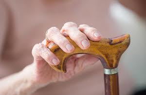 senior woman's hands holding her walking stick