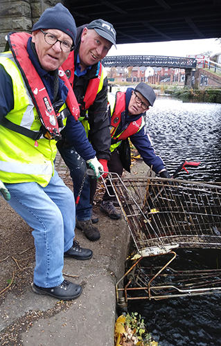 Canal and River Trust volunteers Len Weeks, Joe Harrison and Jim Carr hauling a shopping trolley out of the water - Credit Nigel Heath